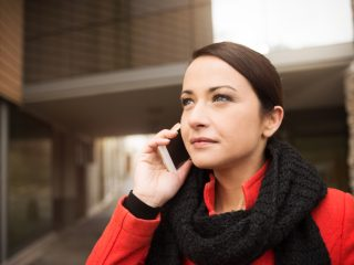 Smiling woman in red coat having a phone call with her smart phone, city buildings on background